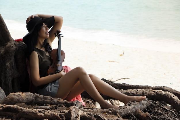 Beautiful woman sitting on the beach Premium Photo