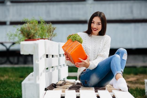 Bella donna seduta su una panchina e tenendo tra le mani un regalo Foto Gratuite