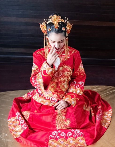 The beautiful woman sitting on ground floor,wearing chinese costume,portrait of model posing,new year festival Premium Photo