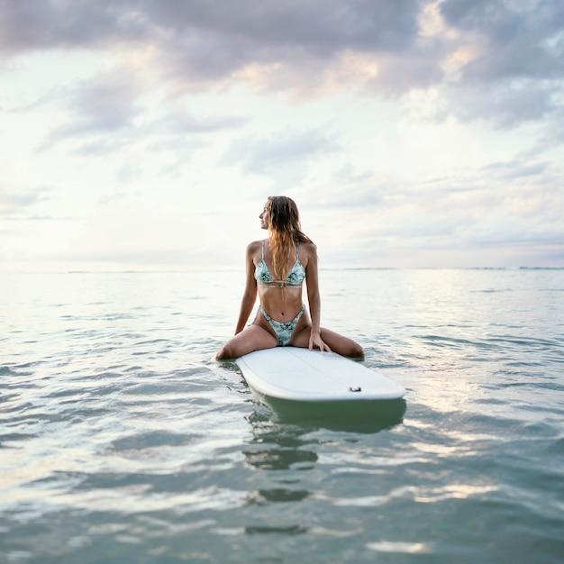 Красивая женщина сидит на доске для серфинга в воде Premium Фотографии