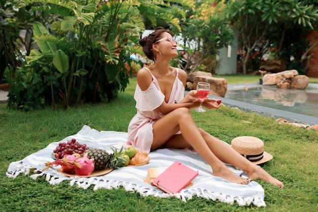 毛布の上に座って、ワインを飲んで、トロピカルガーデンで夏のピクニックを楽しんでいる美しい女性。 無料写真