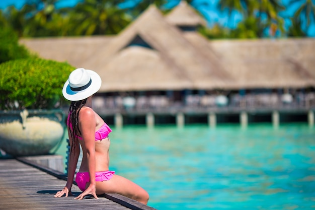 Beautiful woman sitting on wooden jetty at tropical resort Premium Photo