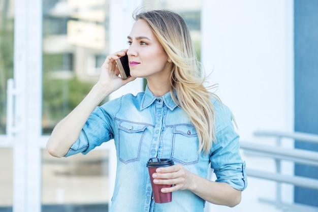 Красивая женщина говорит по телефону и пьет кофе Premium Фотографии