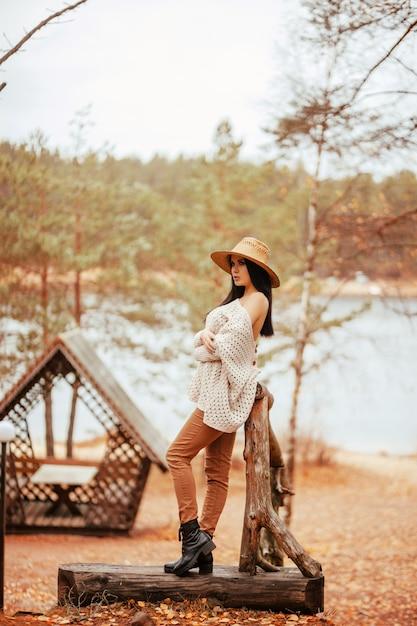 Beautiful woman standing near the lake, wooden arbor and stairway Premium Photo