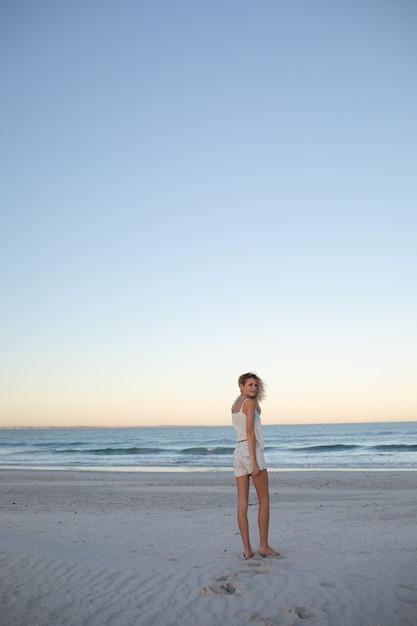 Красивая женщина, стоящая на пляже Бесплатные Фотографии