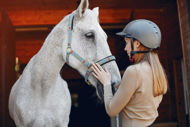 Beautiful woman standing with a horse Free Photo