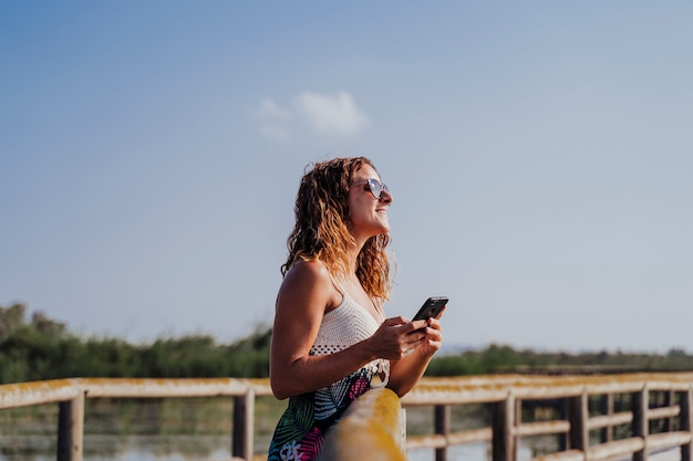 Beautiful woman standing on a wood pier and using mobile phone Premium Photo