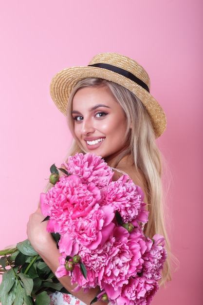 Beautiful woman in straw hat with flowers peonies in hands on pink wall Premium Photo