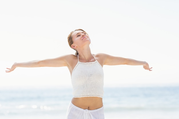 Beautiful woman stretching her arms on the beach Premium Photo