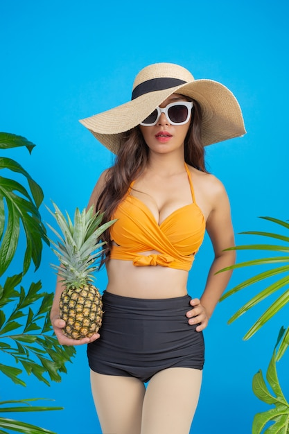 Beautiful woman in a swimsuit holding a pineapple on blue Free Photo