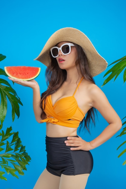 Beautiful woman in a swimsuit holding a watermelon on blue Free Photo