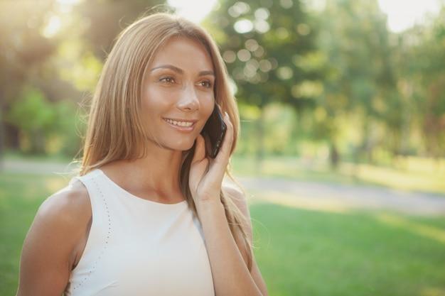 Beautiful woman talking on the phone outdoors Premium Photo