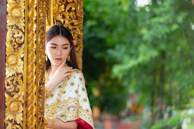 Bella donna in abito tradizionale tailandese sorridente e in piedi al tempio Foto Gratuite