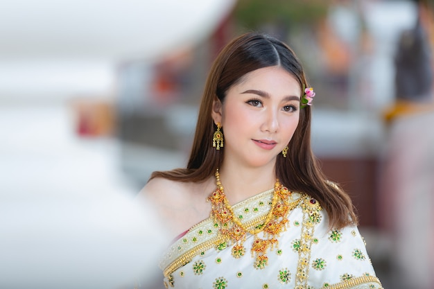 Beautiful woman in thai traditional outfit smiling and standing at temple Free Photo