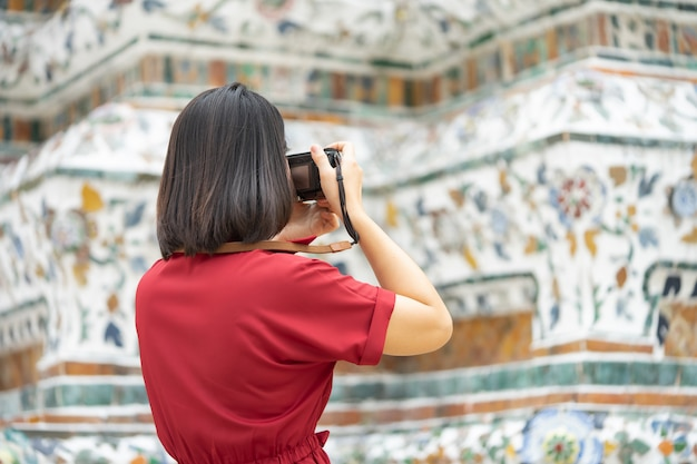 Beautiful woman tourist hold camera to capture the memories Premium Photo