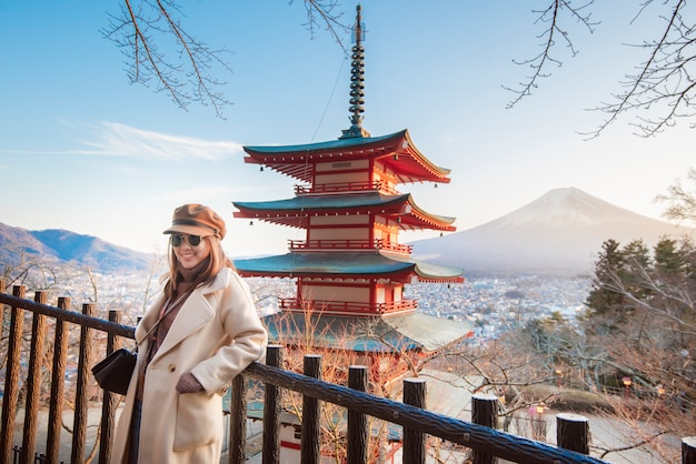 Beautiful woman tourist smiling on chureito pagoda and  fuji mountain, japan Premium Photo