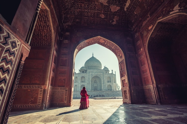 Beautiful woman in traditional dress costume,asian woman wearing typical saree/sari dress identity culture of india. taj mahal scenic the morning view of taj mahal monument  at agra, india. Premium Photo