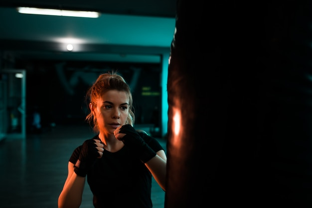 Beautiful woman training with punching bag. close-up. Premium Photo