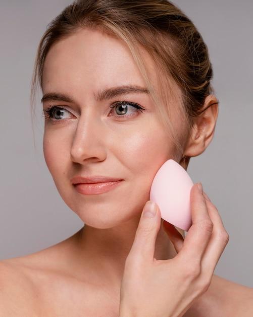 Красивая женщина с помощью блендера для макияжа Бесплатные Фотографии