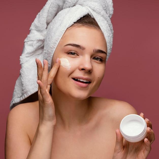 Красивая женщина, используя крем для лица Бесплатные Фотографии
