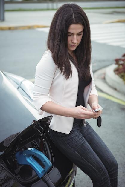 電気自動車を充電しながらモバイルポーンを使用して美しい女性 無料写真