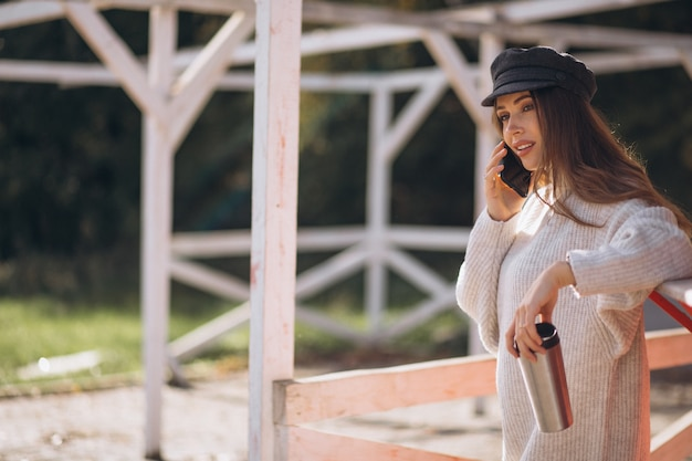 電話を使用してお茶を飲む美しい女性 無料写真