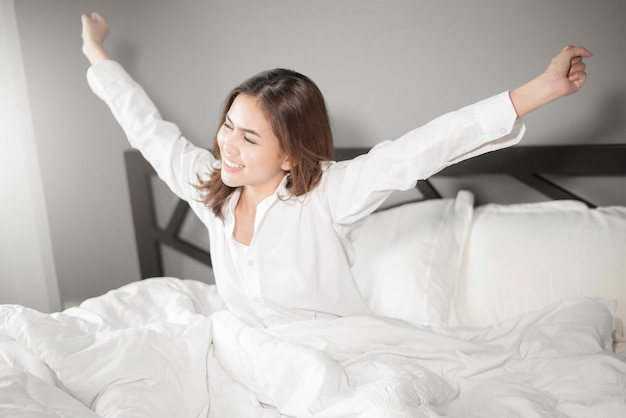 Beautiful woman wake up on bed in morning Premium Photo