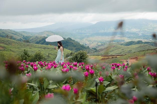 Beautiful woman walking in flower garden. natural landscape. Premium Photo