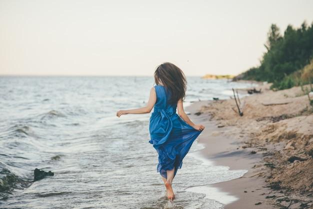 水のビーチの上を歩いて美しい女性 Premium写真