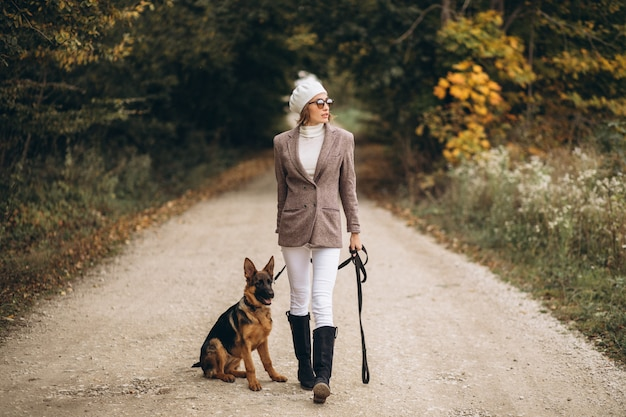 Beautiful woman walking out her dog in autumn park Free Photo