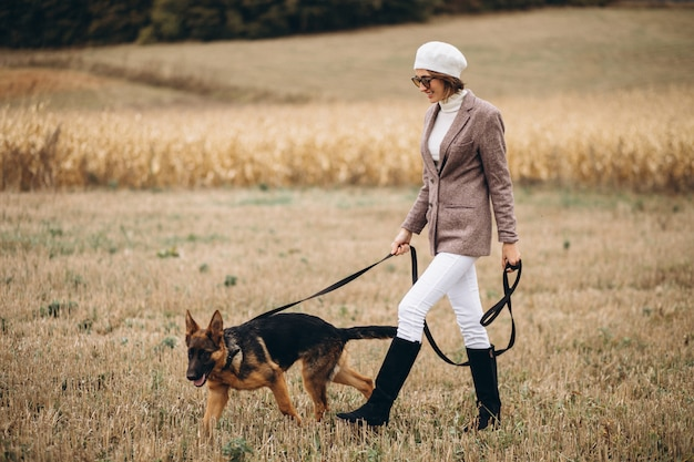 Beautiful woman walking out her dog in a field Free Photo