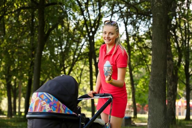 Красивая женщина гуляет с ребенком в парке Premium Фотографии