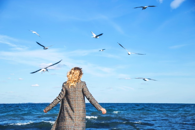 Beautiful woman walks in autumn and practices mindfulness by the sea with seagulls. Premium Photo