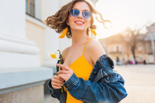 Bella donna che ondeggia i capelli sorridente, abbigliamento elegante, indossa giacca di jeans e top giallo, tendenza della moda, stile estivo, umore positivo felice, giornata di sole, alba, moda di strada, occhiali da sole blu Foto Gratuite