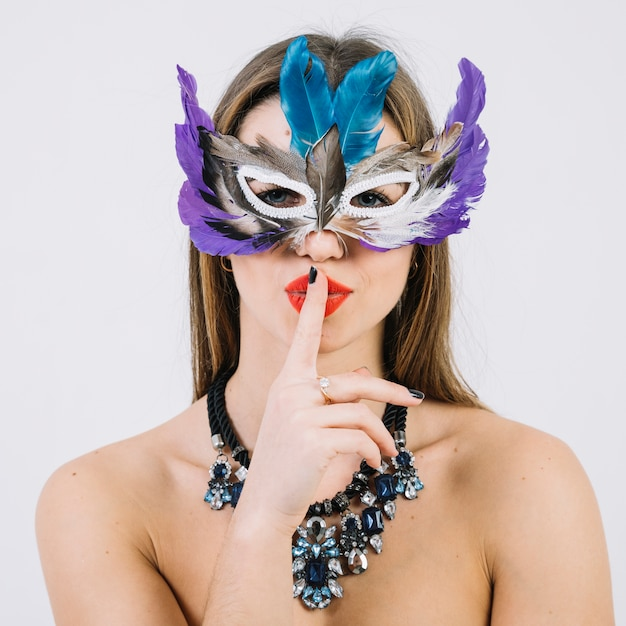Beautiful woman wearing feather mask with finger on her lips Free Photo