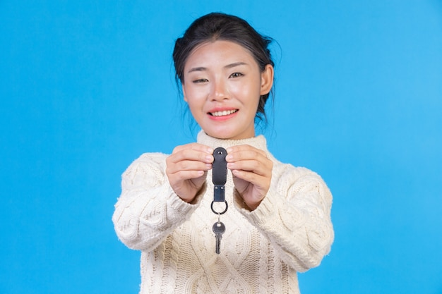 Beautiful woman wearing a new long sleeved white carpet, holding a key ring in the hand on a blue . trading  s. Free Photo