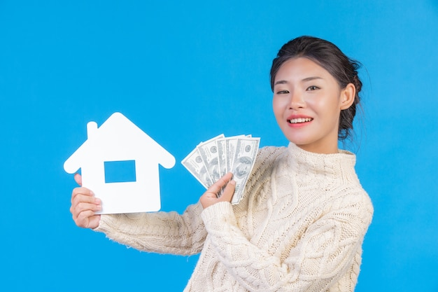 A beautiful woman wearing a new long sleeved white carpet that holds the house symbol and dollar bills on a blue . trading . Free Photo