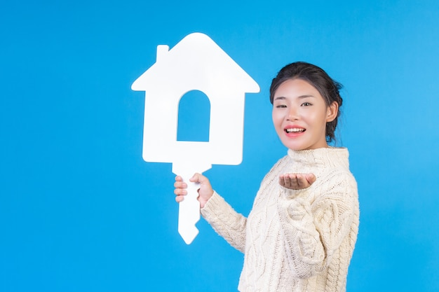 A beautiful woman wearing a new long sleeved white shirt with a house symbol  . house trading . Free Photo