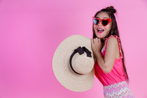 A beautiful woman wearing red glasses with a big hat on a pink . Free Photo