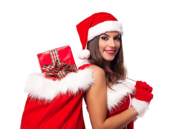 Bella donna che indossa abiti di babbo natale tenendo il sacco pieno di regali di natale Foto Gratuite