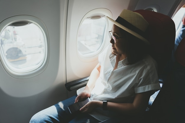 Beautiful woman wearing a straw hat using a smart phone while sitting on the plane Premium Photo