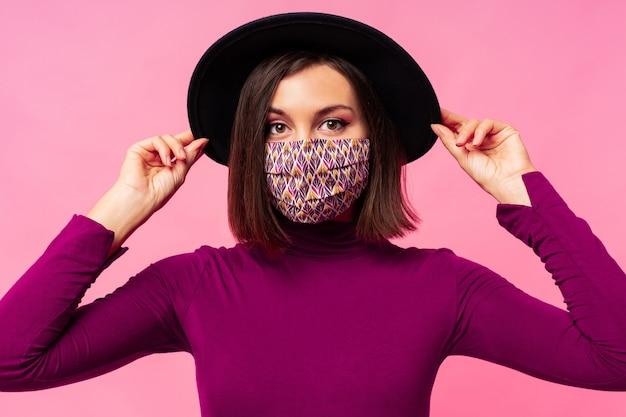 세련 된 얼굴 보호 마스크를 착용하는 아름 다운 여자. 검은 모자 무료 사진