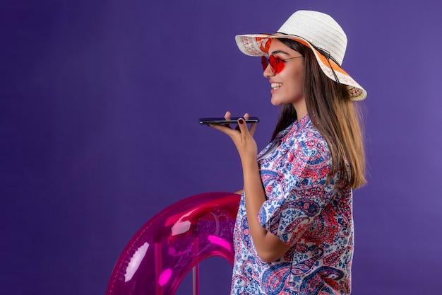 Красивая женщина в летней шляпе и красных солнцезащитных очках держит надувное кольцо, отправляя голосовое сообщение с помощью мобильного телефона, стоя боком со счастливым лицом над фиолетовым пространством Бесплатные Фотографии