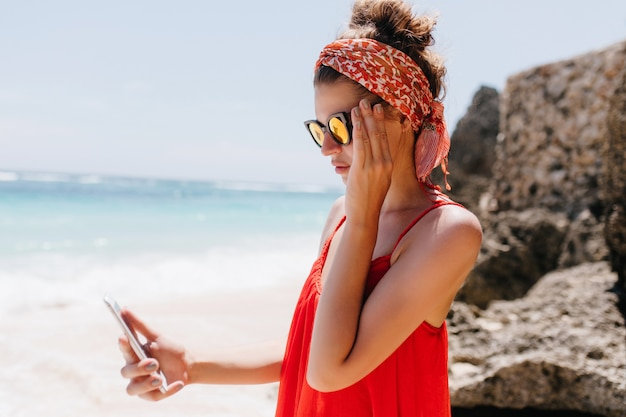 Bella donna indossa occhiali da sole sparkle in piedi vicino a rocce con lo smartphone. elegante ragazza abbronzata in abito rosso guardando lo schermo del telefono mentre si riposa in spiaggia. Foto Gratuite