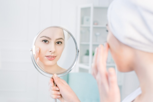 Beautiful woman in white bathrobe and towel looking at her perfect skin in mirror and applying tonal cream base on face Premium Photo