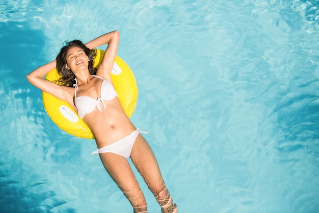 Beautiful woman in white bikini floating on inflatable tube in swimming pool Premium Photo