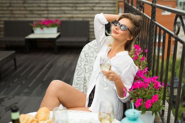 Beautiful woman in a white shirt on the balcony Premium Photo