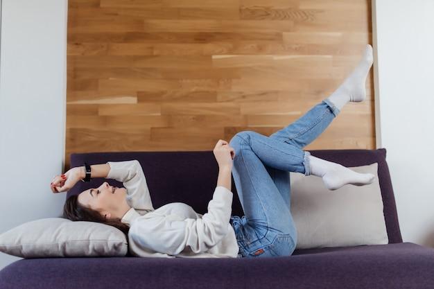 La bella donna in maglione bianco e blue jeans si diverte a cattivo tempo di giorno Foto Gratuite