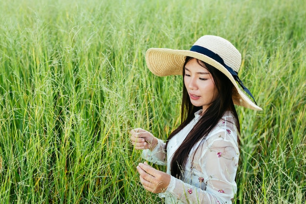 A beautiful woman who is sitting in the grassland happily. Free Photo