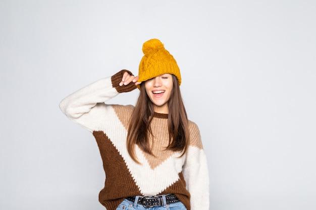 Ritratto di donna bella inverno. ragazza sorridente che porta i vestiti caldi divertendosi cappello e maglione isolati sulla parete bianca Foto Gratuite